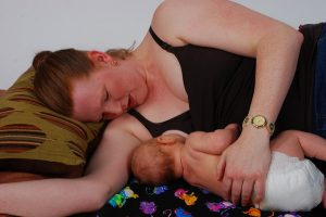 postpartum woman side-lying nursing